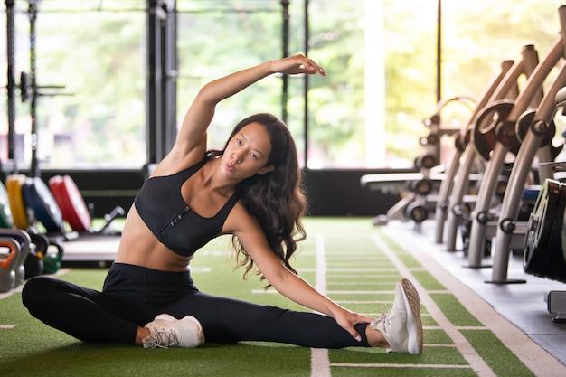 Joven asiática calentando antes de yoga en el gimnasio deportivo