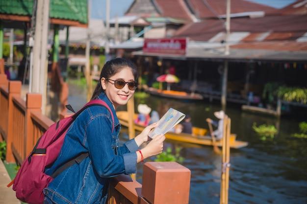 Joven asiática caminando en el mercado flotante de dumonoe saduak, tailandia
