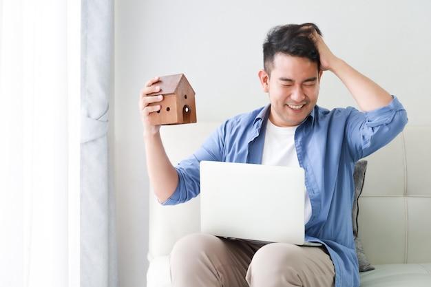 Joven asiática en camisa azul con computadora portátil y modelo de casa pequeña mostrando para préstamo bancario por concepto de casa en sala de estar