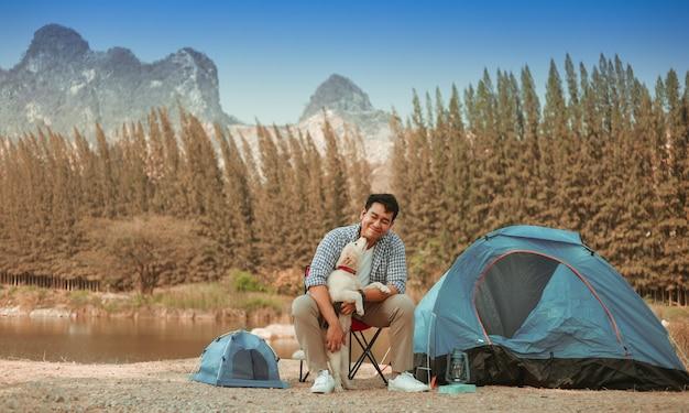 Joven asiática en camisa azul con lindo perrito acampando en la vista de la montaña de lake hill feliz y disfruta de la vida