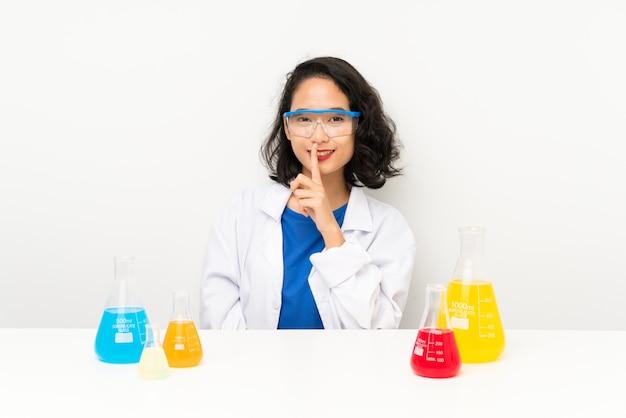 Joven asiática científica haciendo gesto de silencio