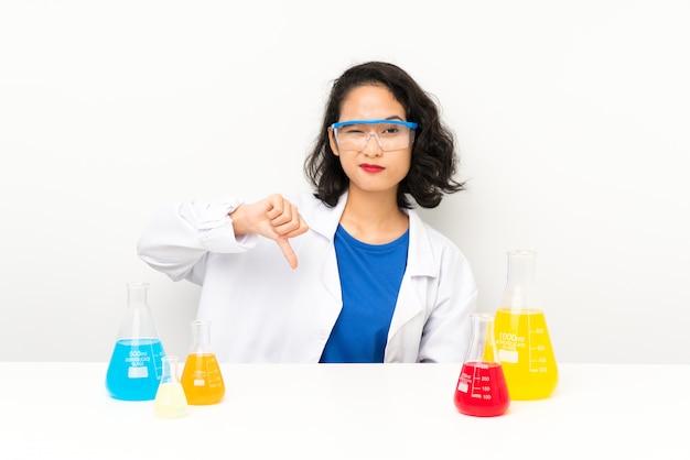 Joven asiática científica mostrando el pulgar hacia abajo signo