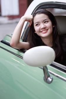 Joven asiática en un coche de época