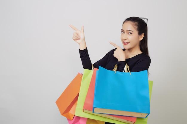 Joven asiática con coloridos bolsos de compras