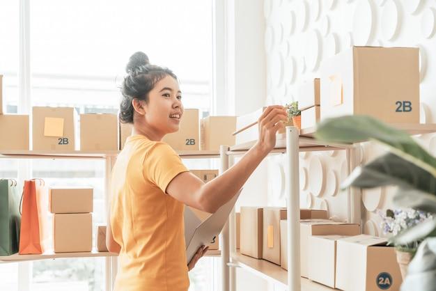 Joven asiática comprobando mercancías en el estante de stock en el almacén