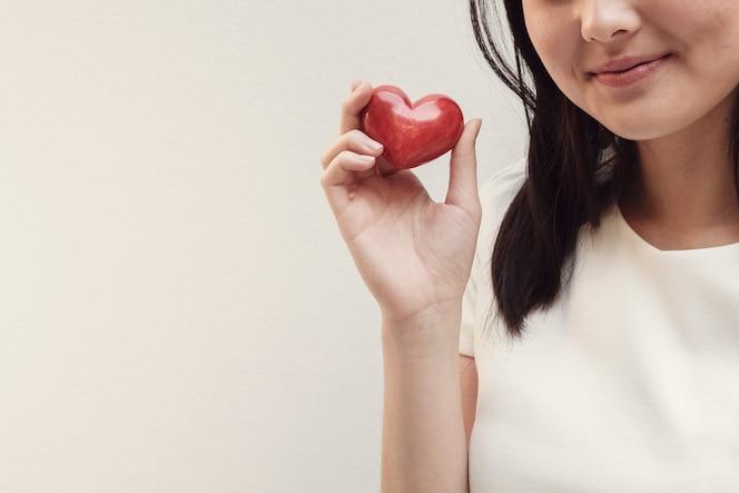 Joven asiática con corazón rojo