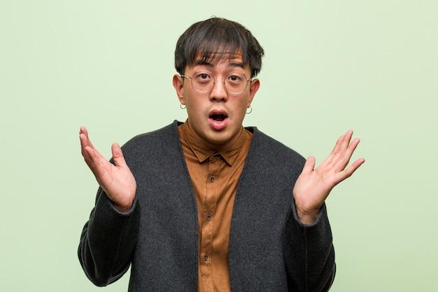 Joven asiática contra una pared verde