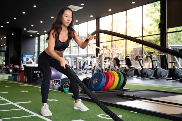 Joven asiática con cuerdas de batalla ejercicio en el gimnasio