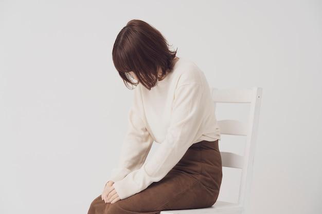 Joven asiática deprimida y bajada para ocultar su rostro con su cabello