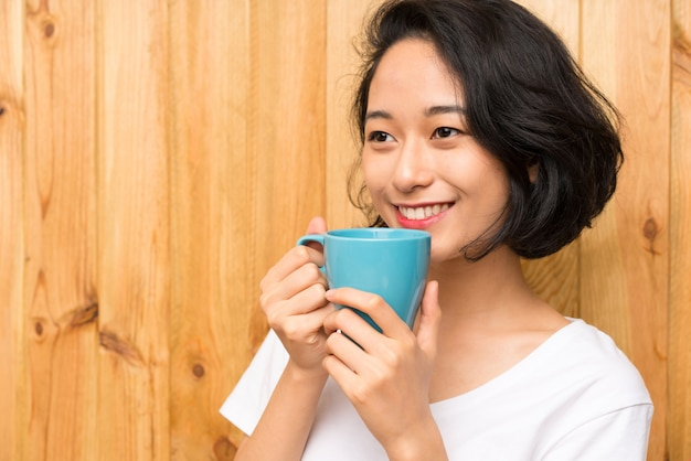 Joven asiática desayunando sosteniendo una taza de café