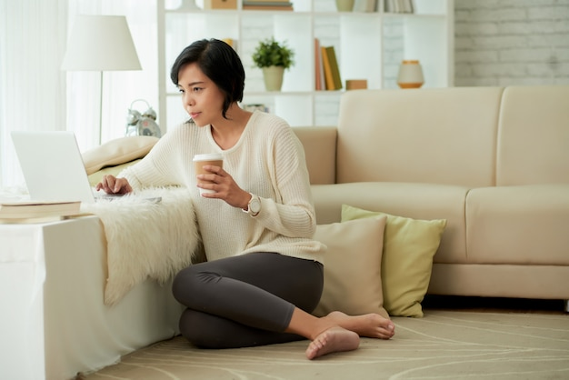 Joven asiática disfrutando de las comodidades del hogar