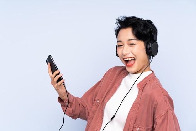 Joven asiática escuchando música y haciendo gesto de guitarra