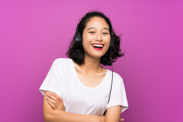 Joven asiática escuchando música con un móvil y cantando sobre pared púrpura aislado