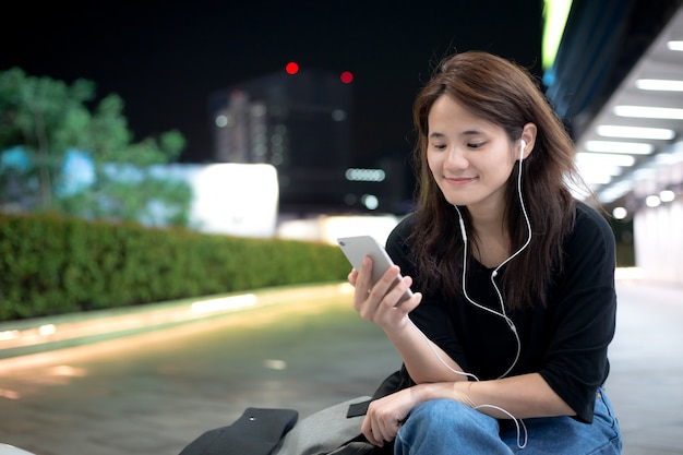 Joven asiática escuchando música o contenido de video a través del teléfono móvil