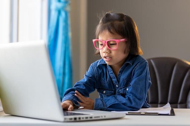 Joven asiática estudiar en línea quedarse en casa en la situación de la enfermedad