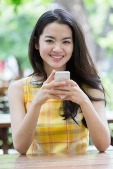 Joven asiática felizmente usando un teléfono inteligente