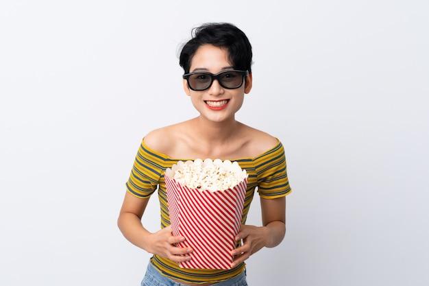 Joven asiática con gafas 3d y sosteniendo un gran cubo de palomitas de maíz