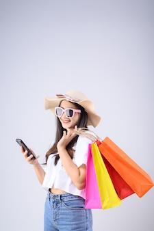 Joven asiática con gafas y sombrero lleva bolsas de la compra mientras juega smartphone sobre fondo blanco.