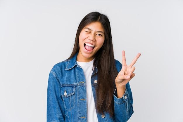 Joven asiática guiña un ojo y tiene un gesto bien con la mano.