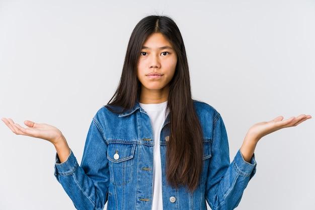 Joven asiática hace escala con los brazos, se siente feliz y segura.