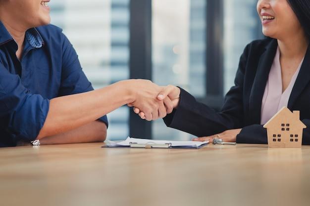 Joven asiática haciendo contrato con agencia de venta de casa de bienes raíces, agente femenino estrechándole la mano con hombre caucásico para obtener contrato y llave de la casa