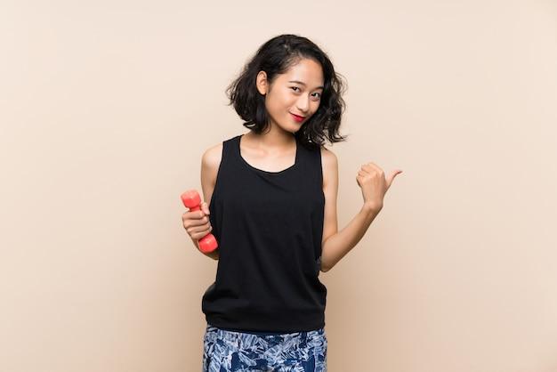 Joven asiática haciendo pesas sobre pared aislada apuntando hacia el lado para presentar un producto