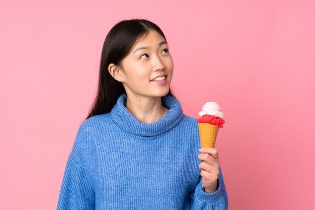 Joven asiática con un helado de cucurucho en la pared rosa mirando hacia arriba mientras sonríe
