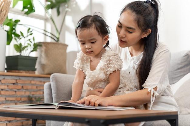 Joven asiática hermosa madre e hija sentada en el sofá y leyendo una historia de libro