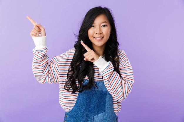 Joven asiática hermosa mujer atractiva posando aislada en el interior apuntando