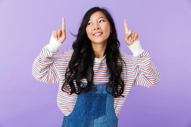 Joven asiática hermosa mujer atractiva posando aislado en el interior apuntando.