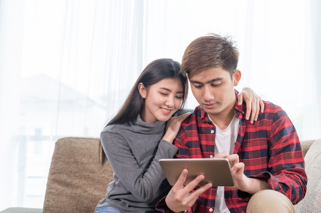 Joven asiática y hombre guapo sentado en el sofá con dispositivo