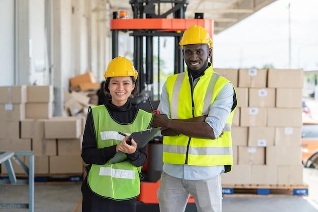 Joven asiática con hombre trabajador en chaleco de seguridad y casco amarillo trabajando en el envío en la fábrica de almacén