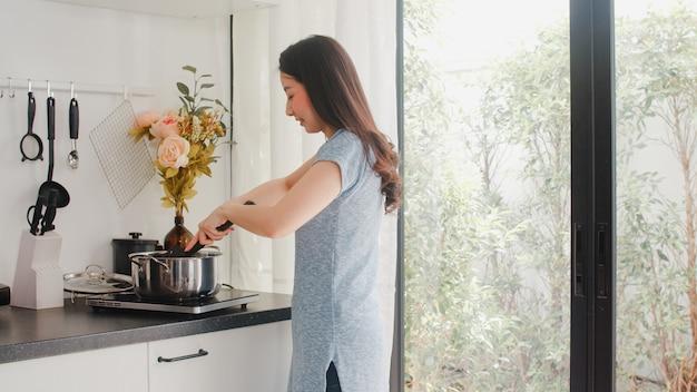 Joven asiática japonesa disfruta de cocinar en casa. mujeres de estilo de vida felices preparando la comida haciendo pasta y espagueti para el desayuno en la cocina moderna en la casa por la mañana.