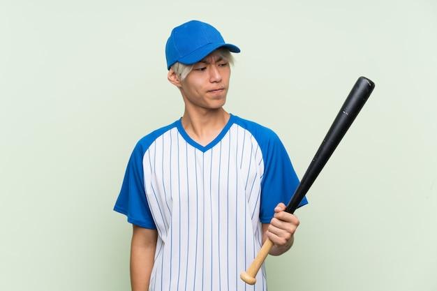 Joven asiática jugando béisbol sobre verde aislado con expresión triste