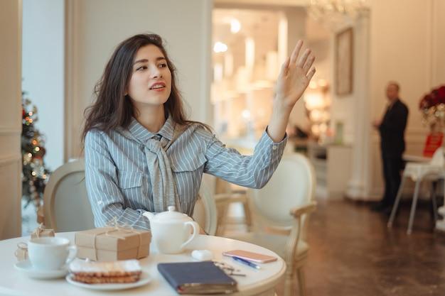Joven asiática llamando a la camarera en café
