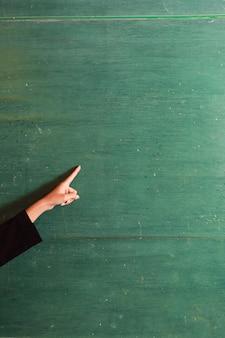 Joven asiática maestra mano señalando algo en el viejo tablero verde