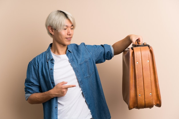 Joven asiática manholding un maletín vintage