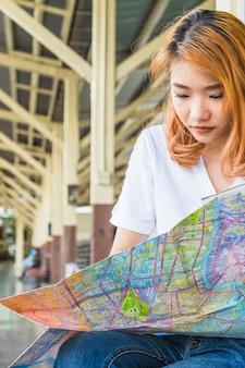 Joven asiática con mapa en plataforma