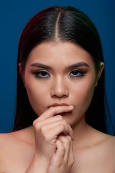 Joven asiática con maquillaje completo y hombros desnudos tocando los labios y mirando a cámara