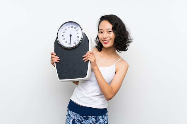 Joven asiática con máquina de pesaje sobre pared blanca aislada