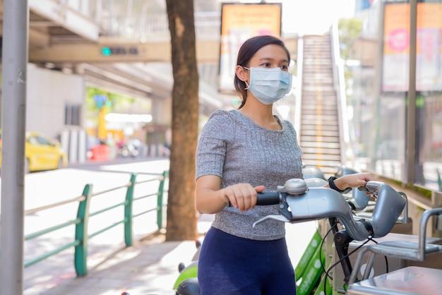 Joven asiática con máscara montando bicicleta en la estación de servicio de bicicletas públicas