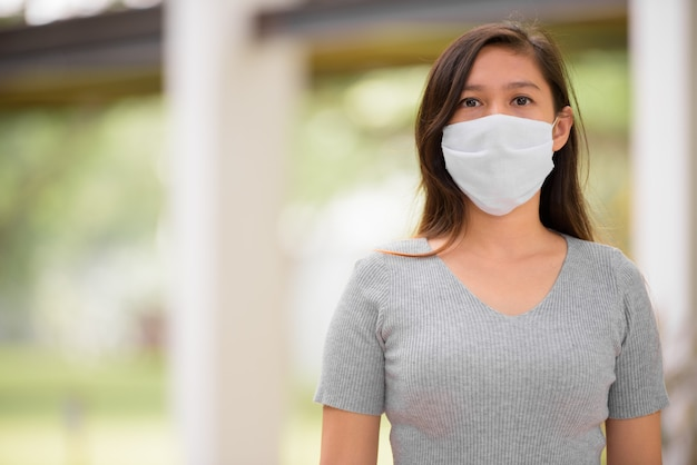 Joven asiática con máscara para protección contra brote de virus corona al aire libre