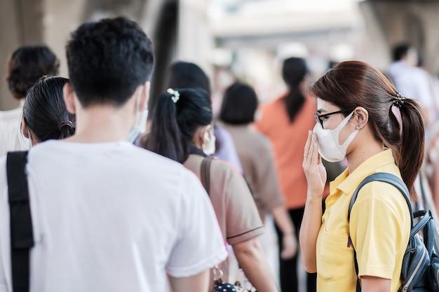 Joven asiática con máscara de protección contra el nuevo coronavirus (2019-ncov) o el coronavirus de wuhan en la estación de tren público, es un virus contagioso que causa infección respiratoria.