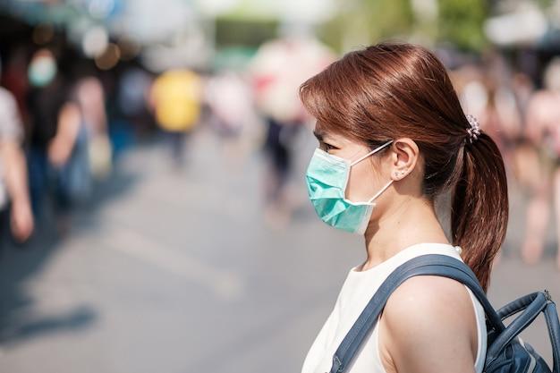 Joven asiática con máscara de protección contra el nuevo coronavirus (2019-ncov) o el coronavirus wuhan en el mercado de fin de semana de chatuchak, punto de referencia y popular para las atracciones turísticas