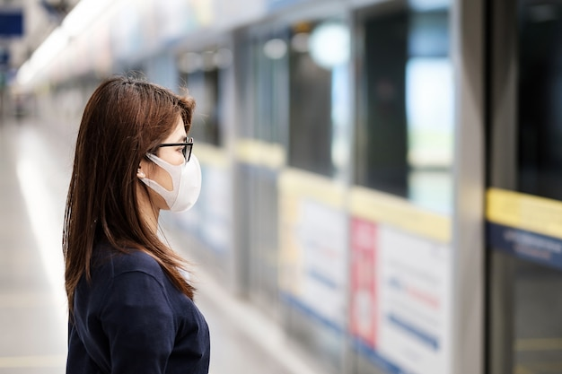 Joven asiática con máscara de protección contra el nuevo coronavirus o la enfermedad del virus corona (covid-19) en el aeropuerto