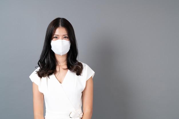 Joven asiática con máscara para proteger el coronavirus en gris