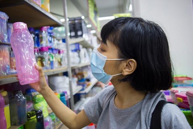 Joven asiática con mascarilla comprando comestibles en el supermercado durante la pandemia del virus