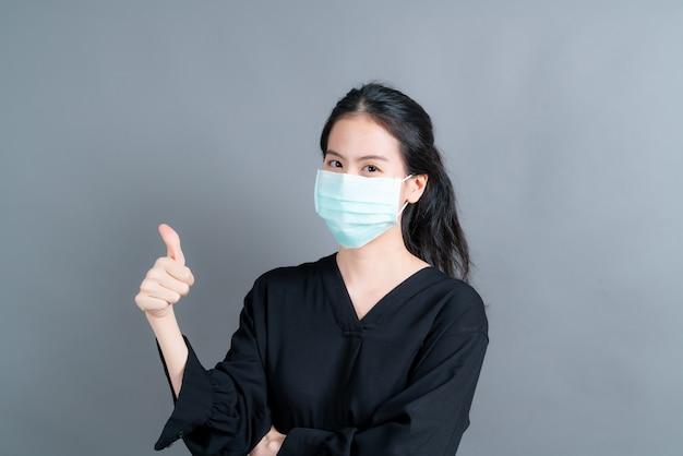 Joven asiática con mascarilla médica protege el polvo del filtro pm2.5 anti-contaminación, anti-smog, covid-19 y dando pulgares hacia arriba