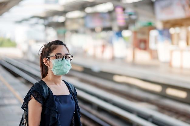 Joven asiática con mascarilla quirúrgica contra el nuevo coronavirus o la enfermedad del virus de la corona (covid-19) en la estación de tren público.