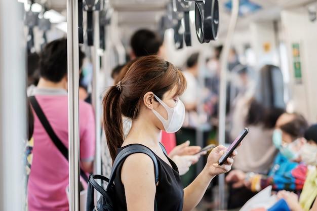 Joven asiática con mascarilla quirúrgica contra el nuevo coronavirus o la enfermedad del virus de la corona (covid-19) en el metro en el interior.